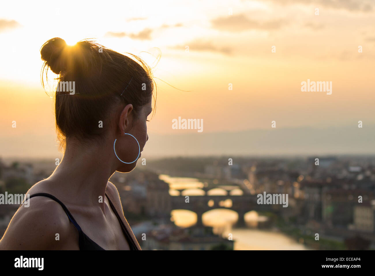 Italy, Tuscany, Young woman and old bridge at sunset - Stock Image