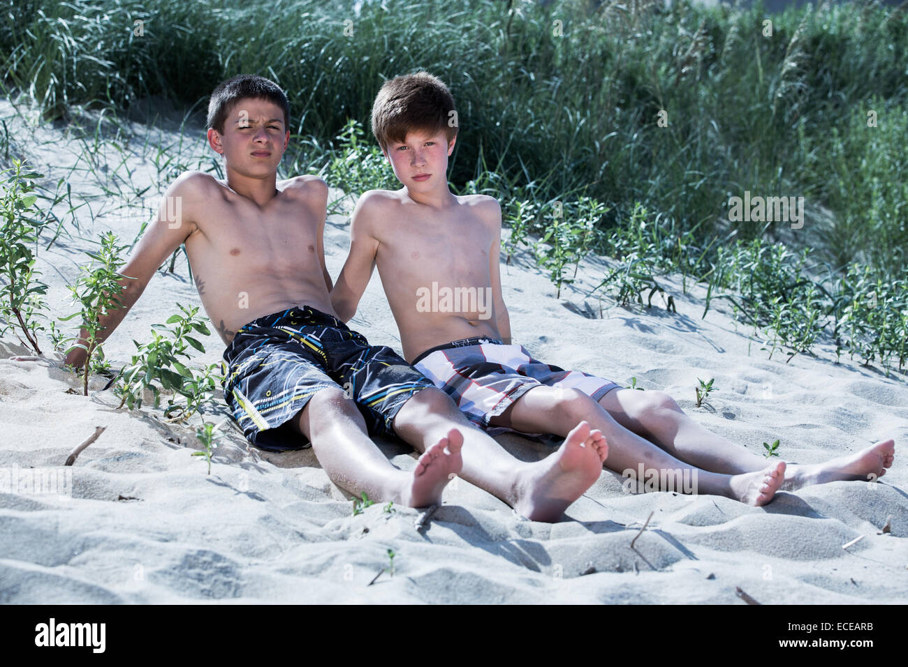 Two boys sitting on the beach - Stock Image