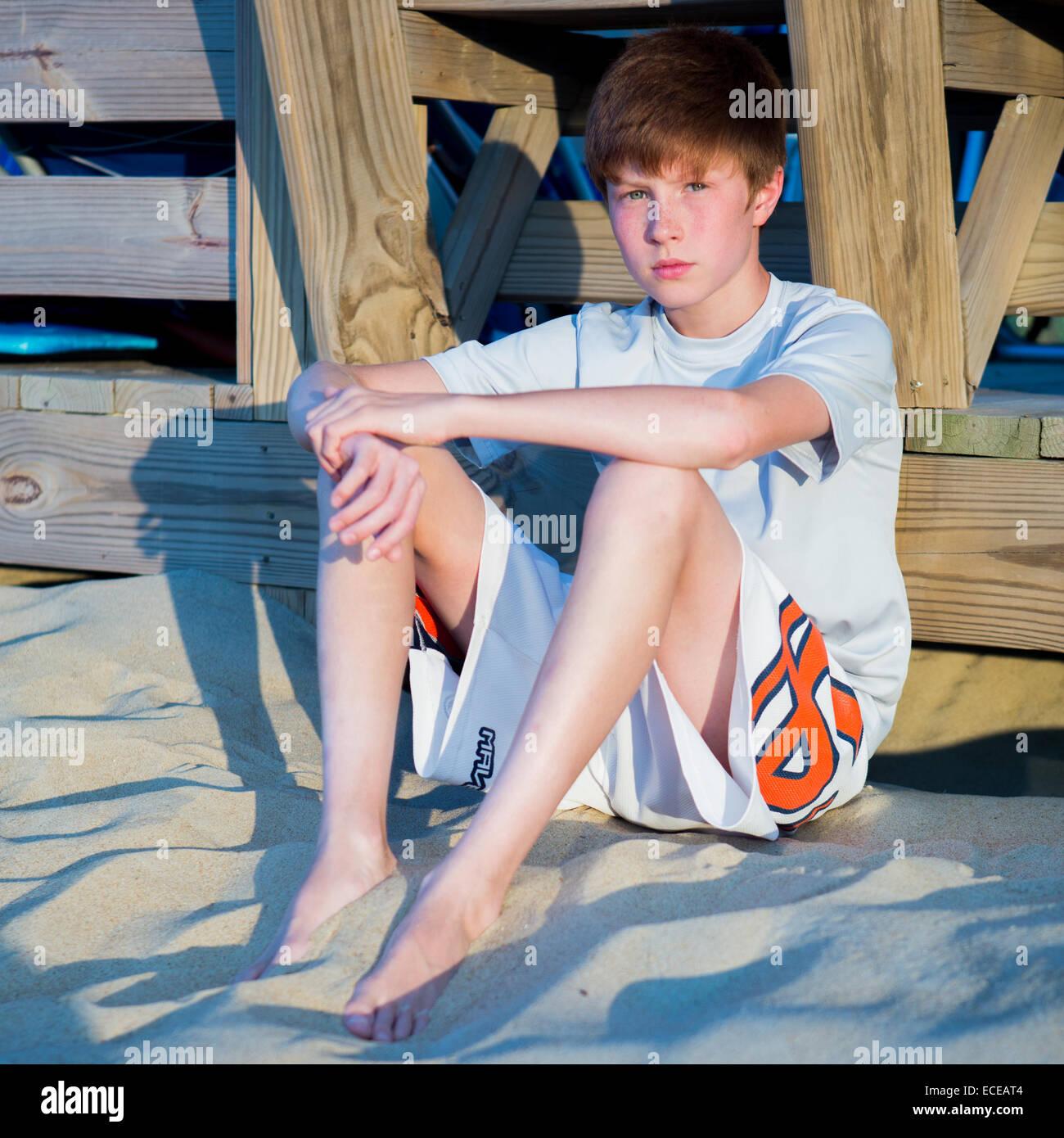 Boy Sitting On Beach Leaning Against Boardwalk Stock Photo