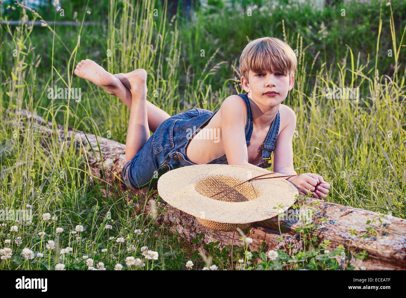 Young boy wearing blue overalls laying on fallen tree - Stock Image