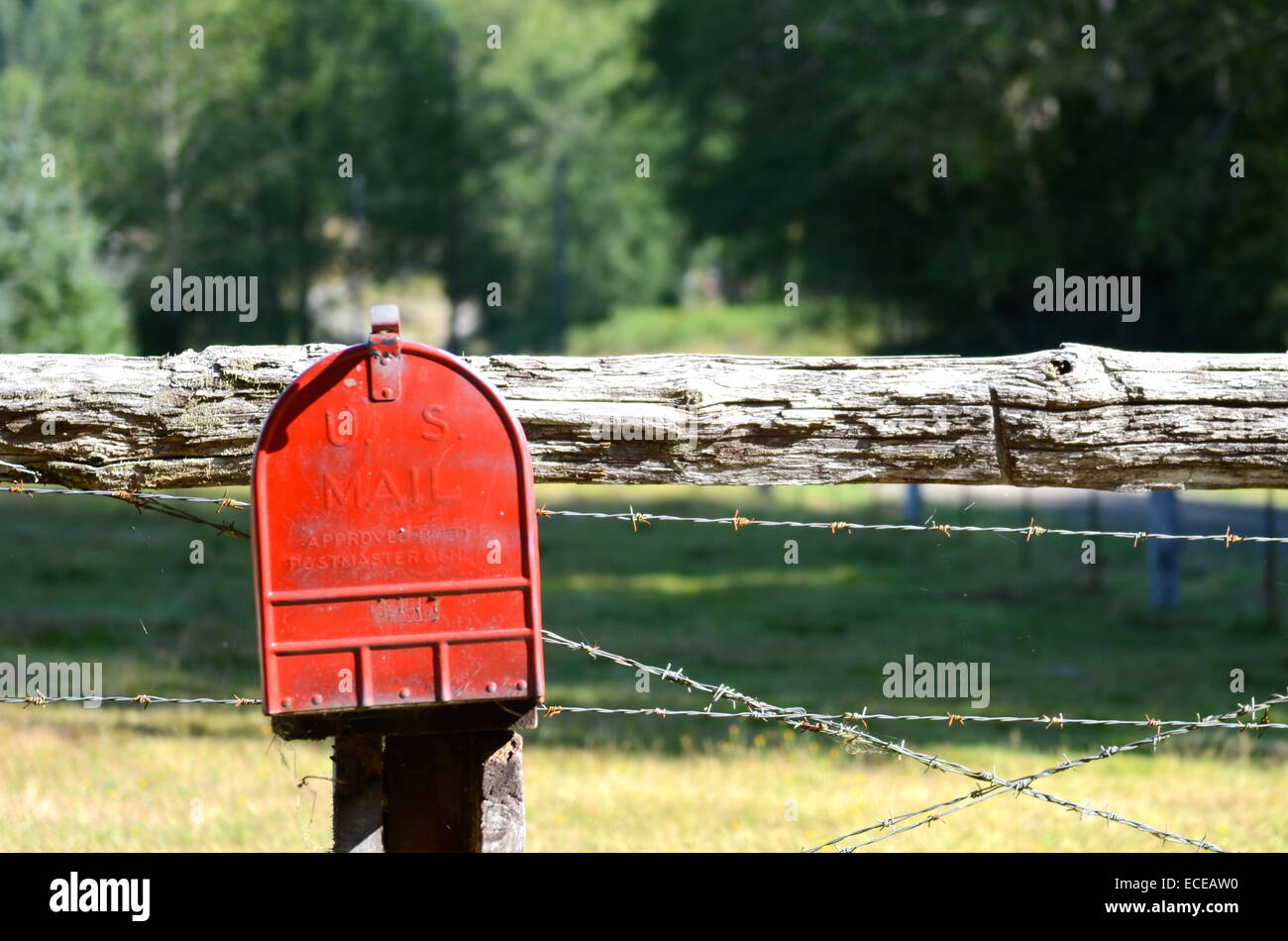 USA, Red mailbox on fencepost - Stock Image