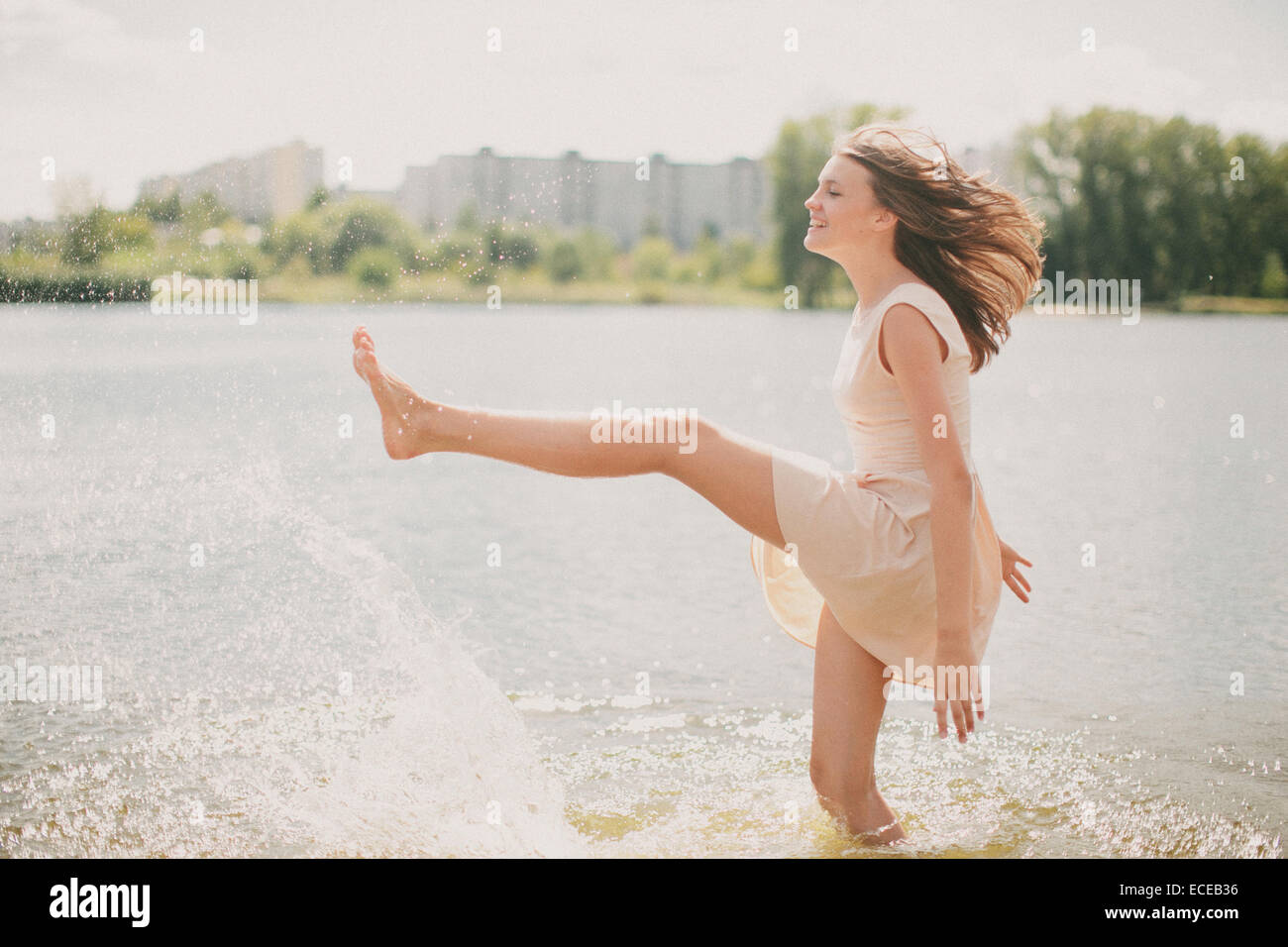 Teenage girl standing in a river kicking water - Stock Image