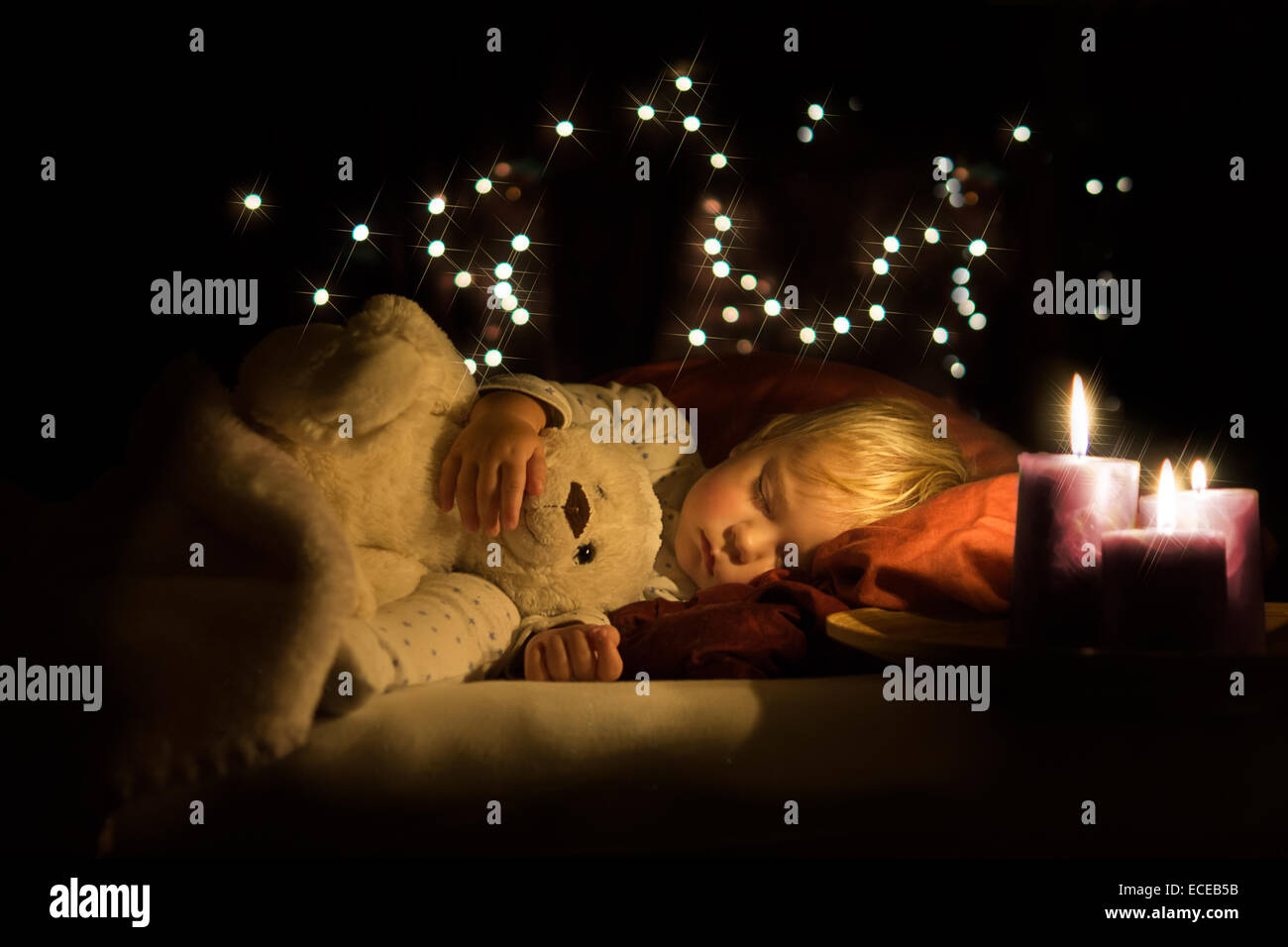 Boy asleep with teddy and warm candle light - Stock Image
