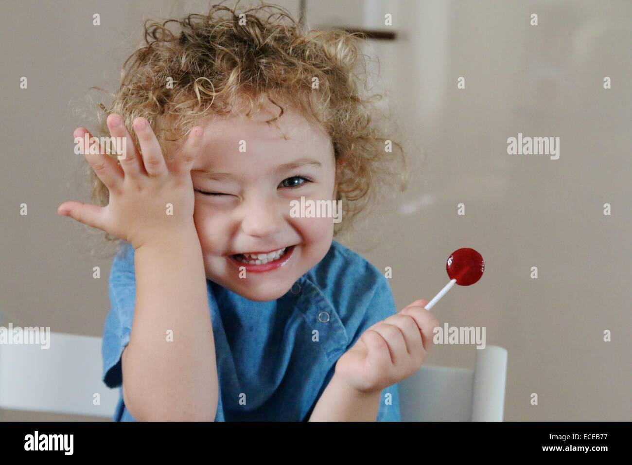 Happy girl eating a lollipop and touching her face Stock Photo