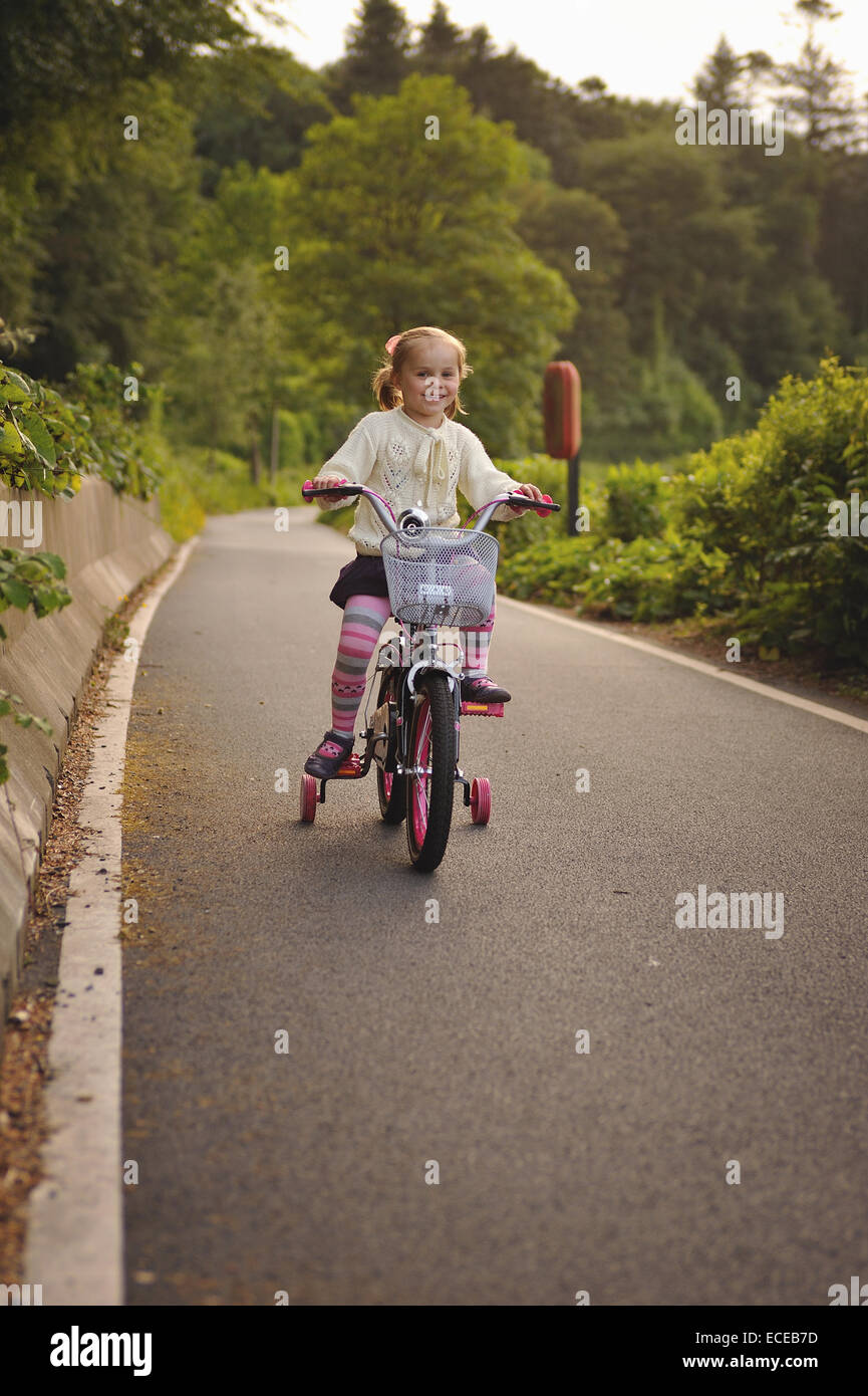 Girl (2-3) riding bicycle - Stock Image
