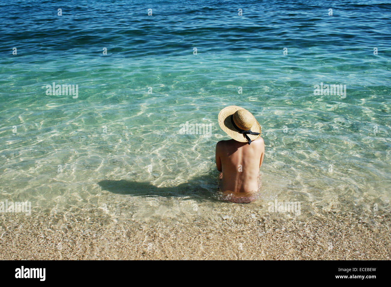 Croatia, Krk Island, Stara Baska boot topping, Woman sitting in water - Stock Image