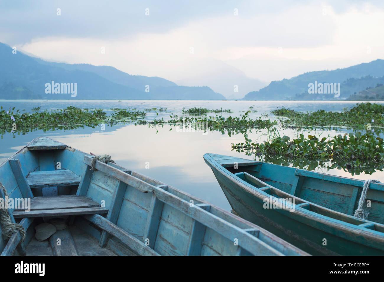 Nepal, Phewa, Cropped shot of two rowboats in mountain lake - Stock Image