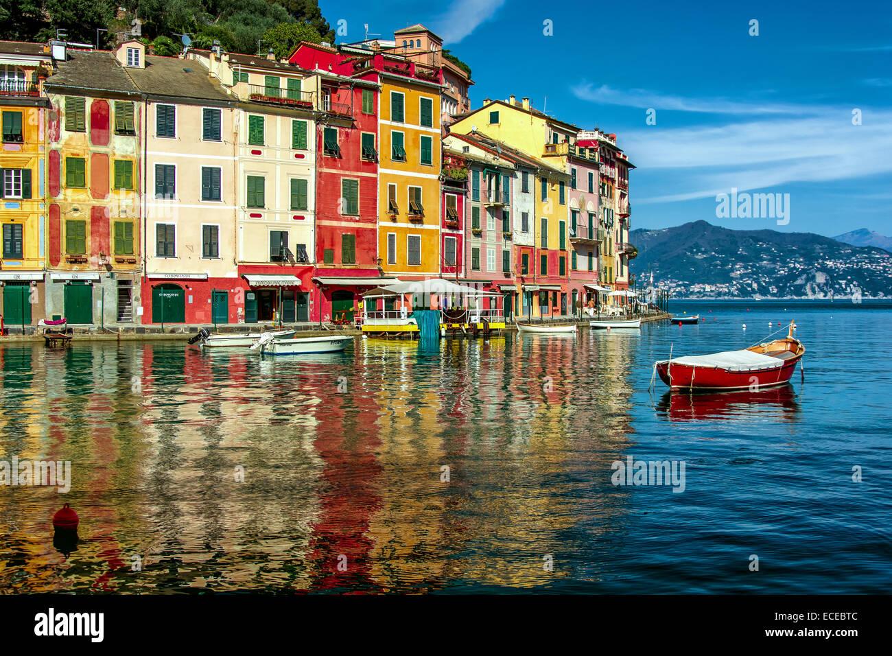 Italy, Liguria, Geneva, Portofino, Multicolored waterfront houses and harbor with anchored motor boats Stock Photo