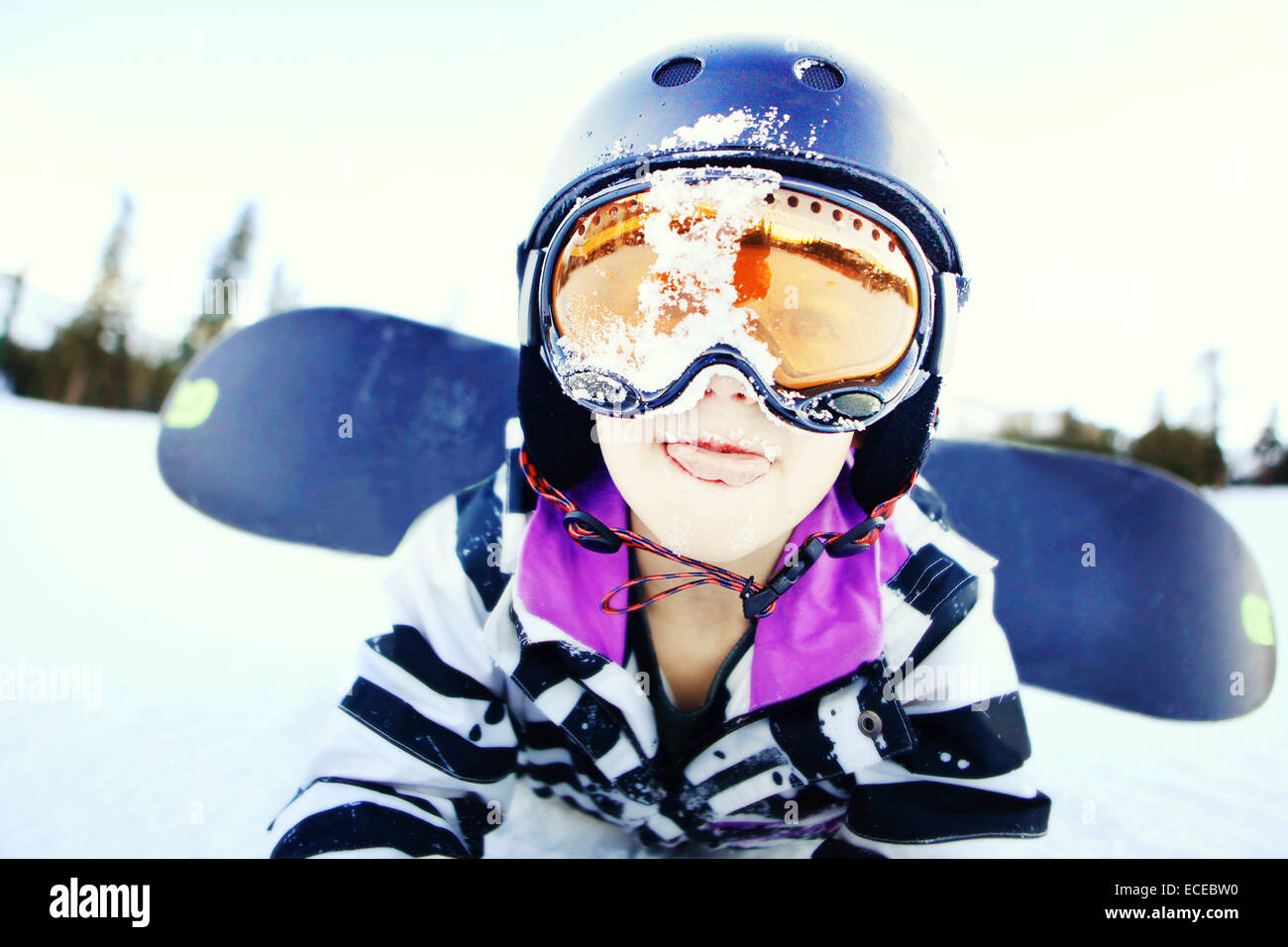 Portrait of boy lying on front with a snowboard - Stock Image