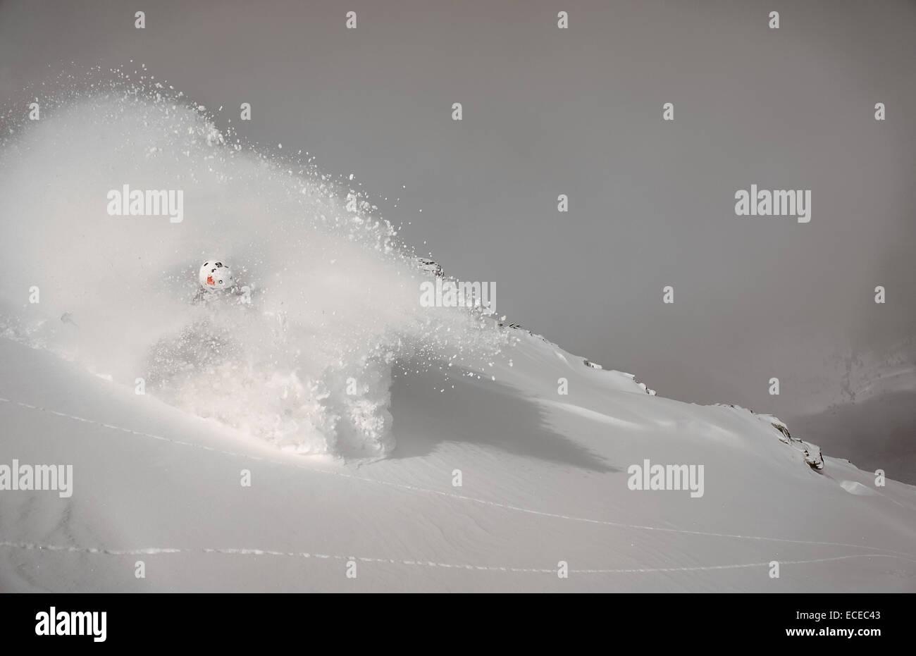 Austria, Salzburg, Gastein, Skier descending slope in cloud of powder snow - Stock Image
