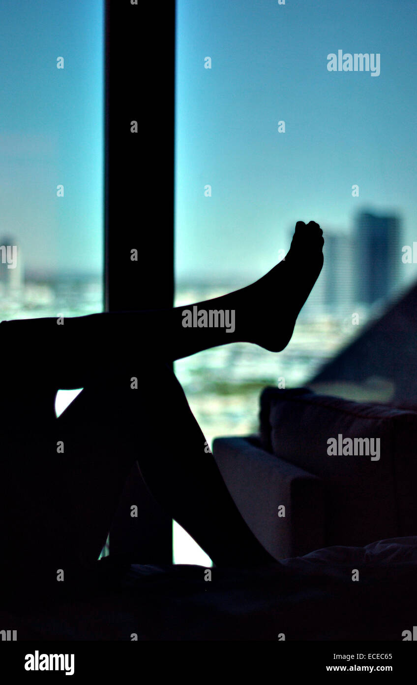 Silhouette of woman's leg against window - Stock Image
