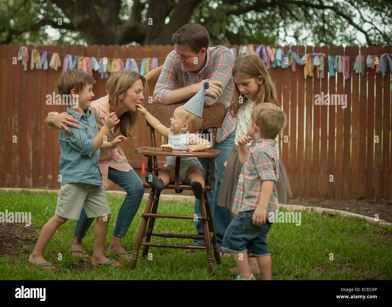 Family celebrating baby boys' first birthday in back yard - Stock Image