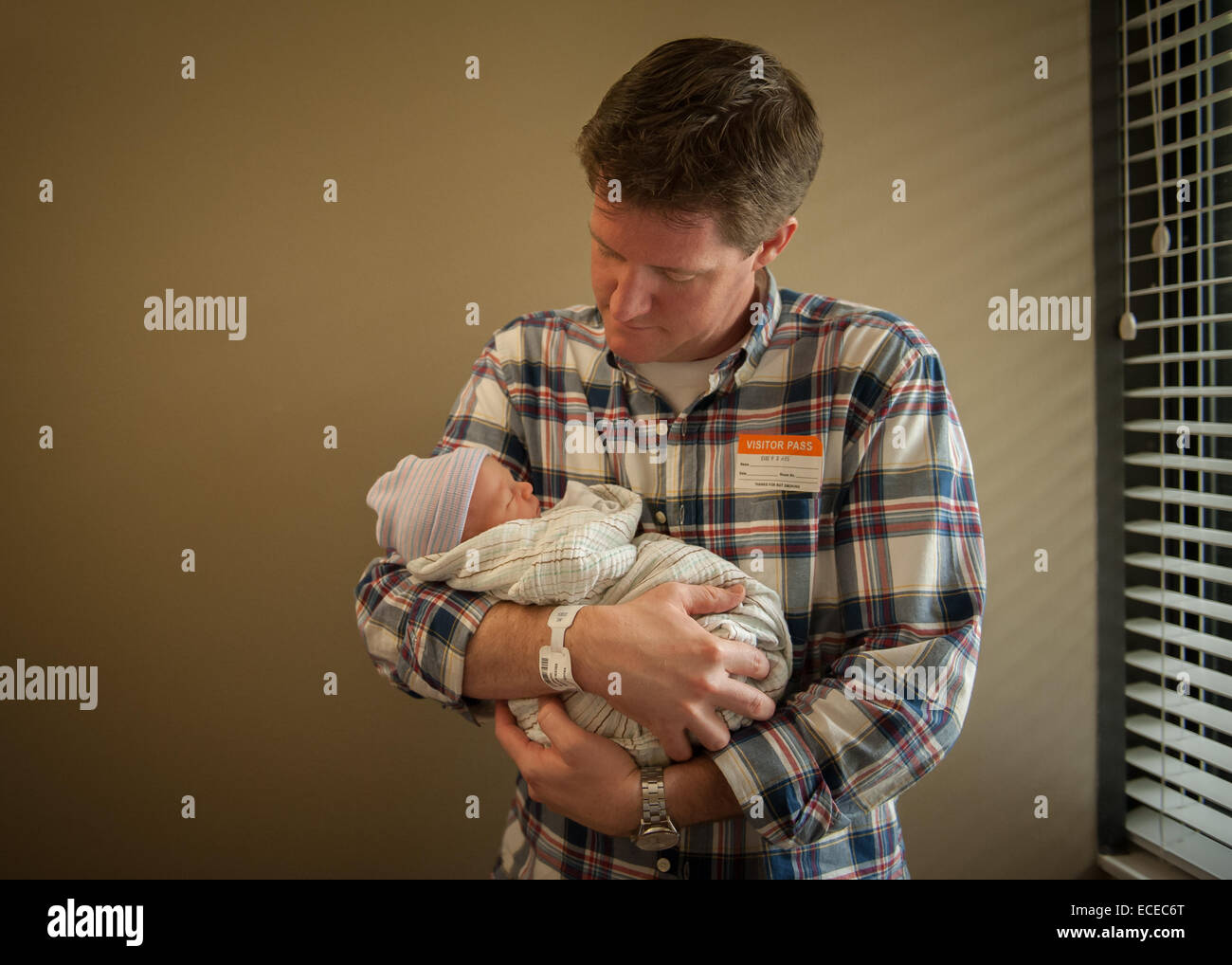 Father holding newborn baby in hospital Stock Photo