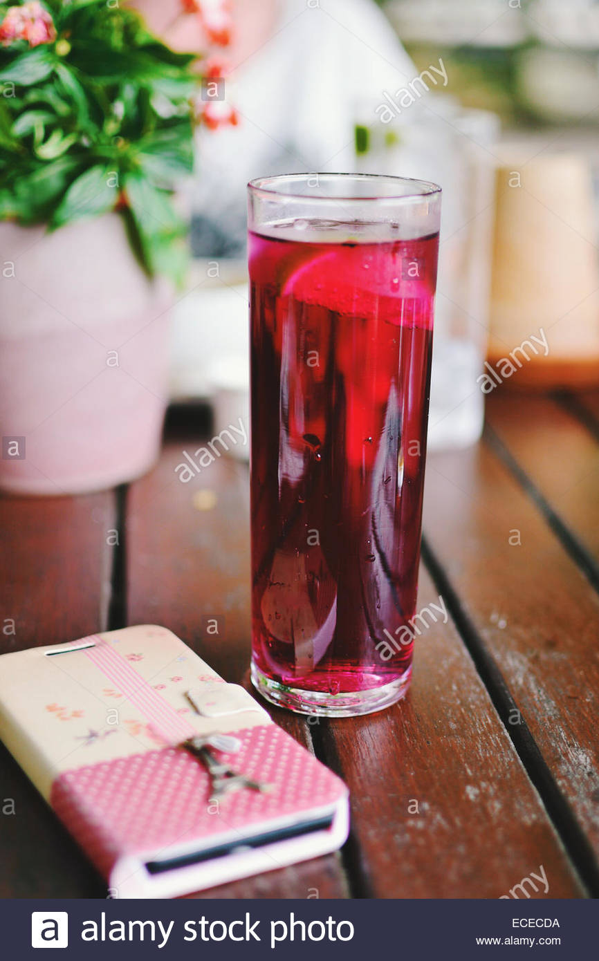 Tall glass of pink drink with lime in restaurant next to smart phone - Stock Image