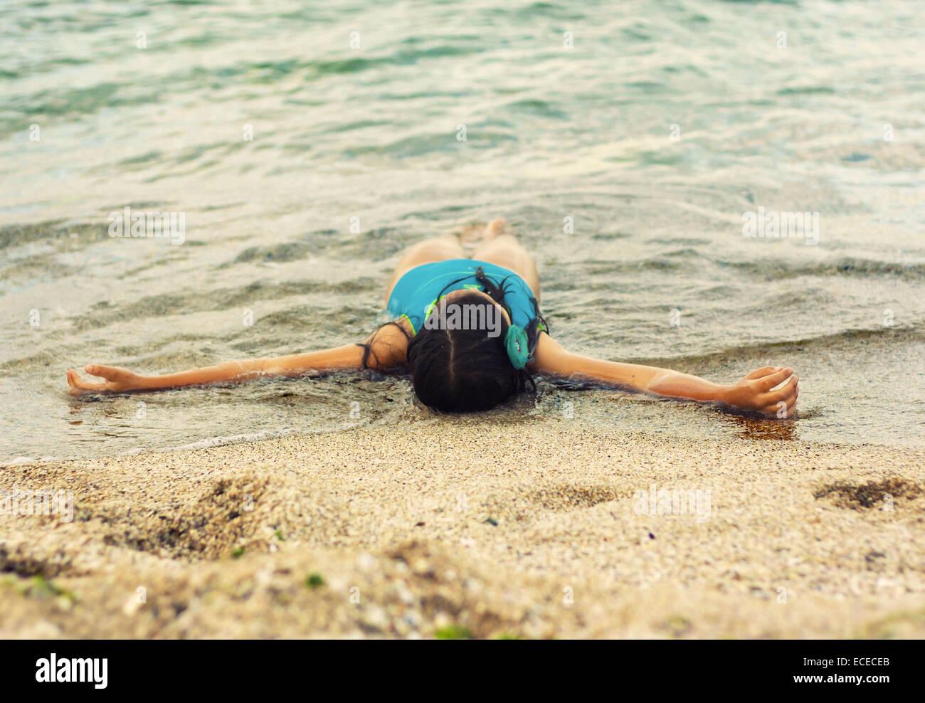 Little girl (6-7) lying on beach in waves - Stock Image