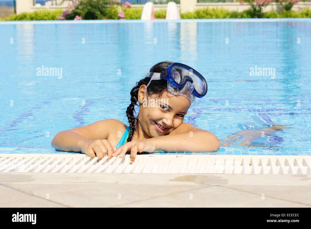 Smiling cute little girl (6-7) having fun in swimming pool - Stock Image