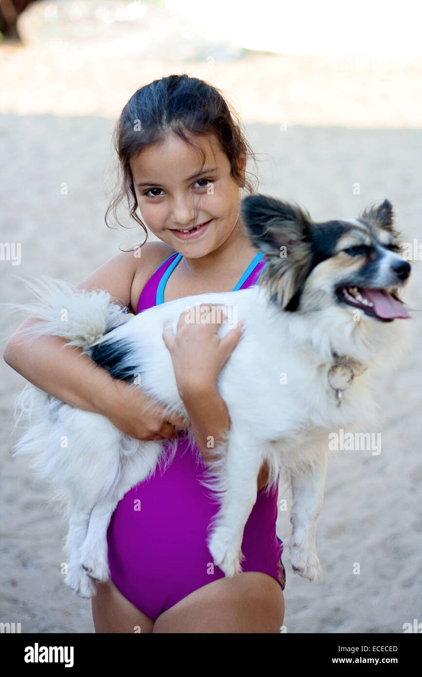 Happy girl (6-7) hugging dog on beach - Stock Image
