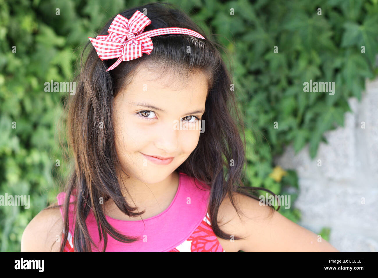Sweet smiling little girl (6-7) with long dark hair on green ivy background - Stock Image