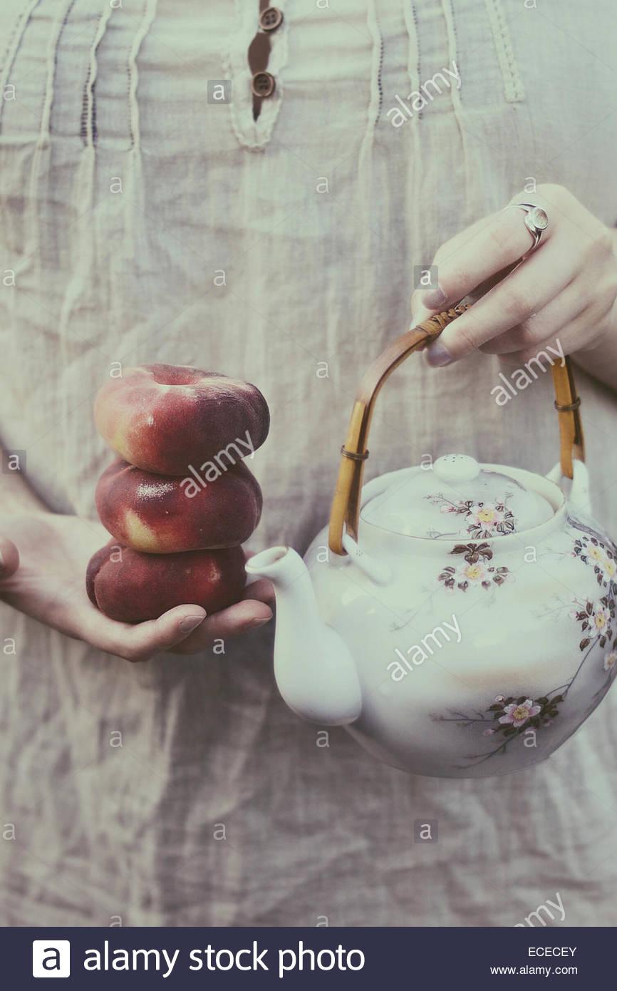 United Kingdom, England, Warwickshire, Stratford-upon-Avon, Woman holding peaches and oriental tea pot - Stock Image