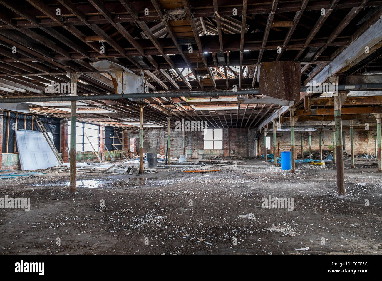 Inside an old Lancashire cotton mill showing decay in the roof structure, with metal supports for the roof - Stock Image
