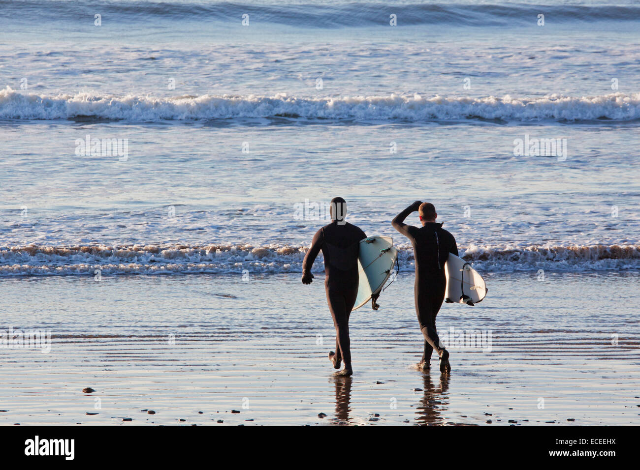 Two surfers on Saunton sands UK prior to entering the water to begin a session riding the waves - Stock Image