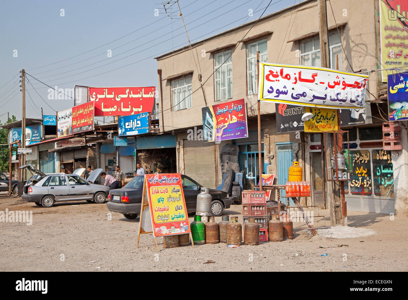 Iranians working on car in primitive garage, repair shops and grocery shop in village in Iran - Stock Image