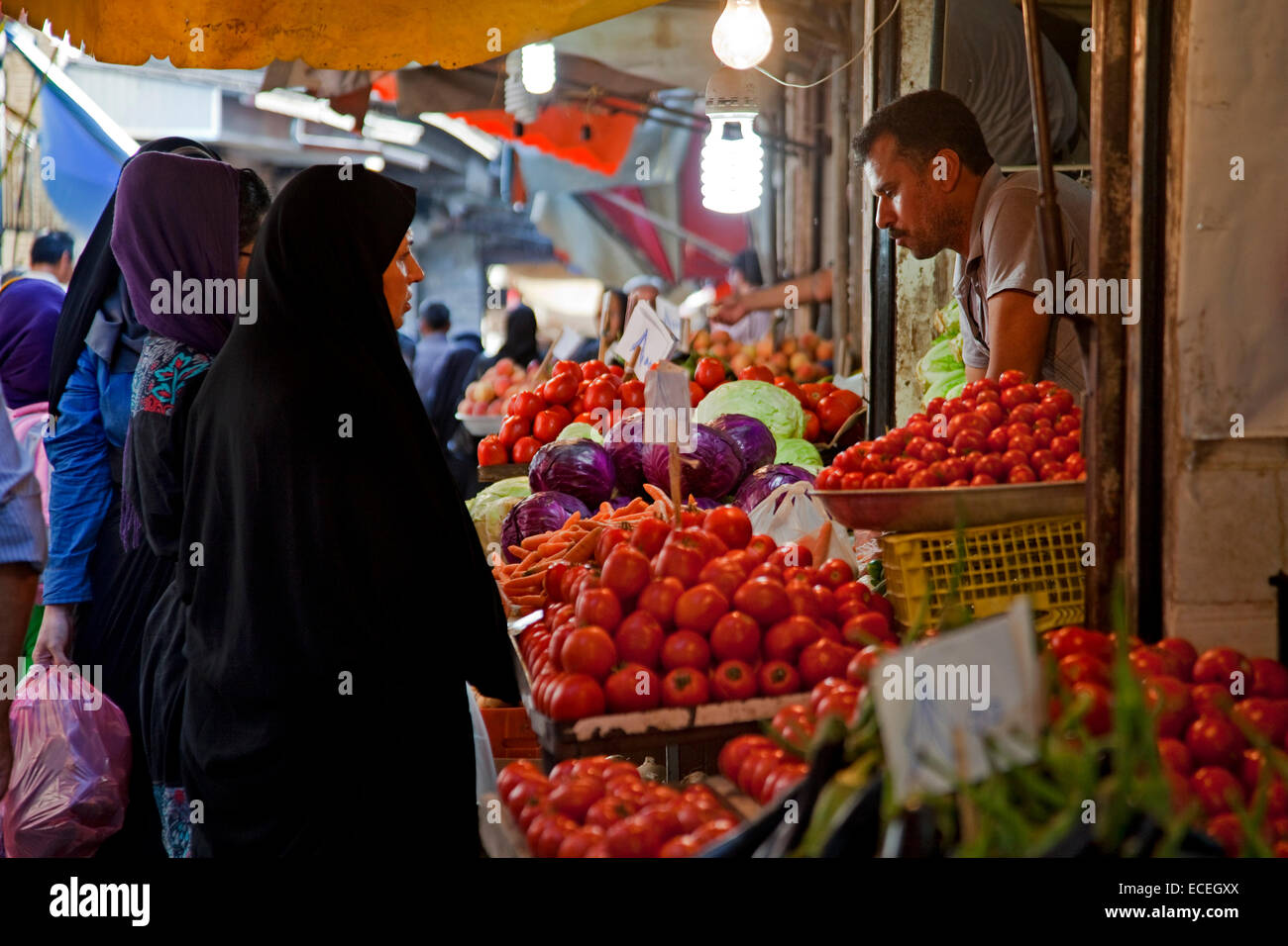 Iranian Muslim women wearing scarves buying vegetables and red tomatoes at food market booth in Gorgan / Gurgan, - Stock Image