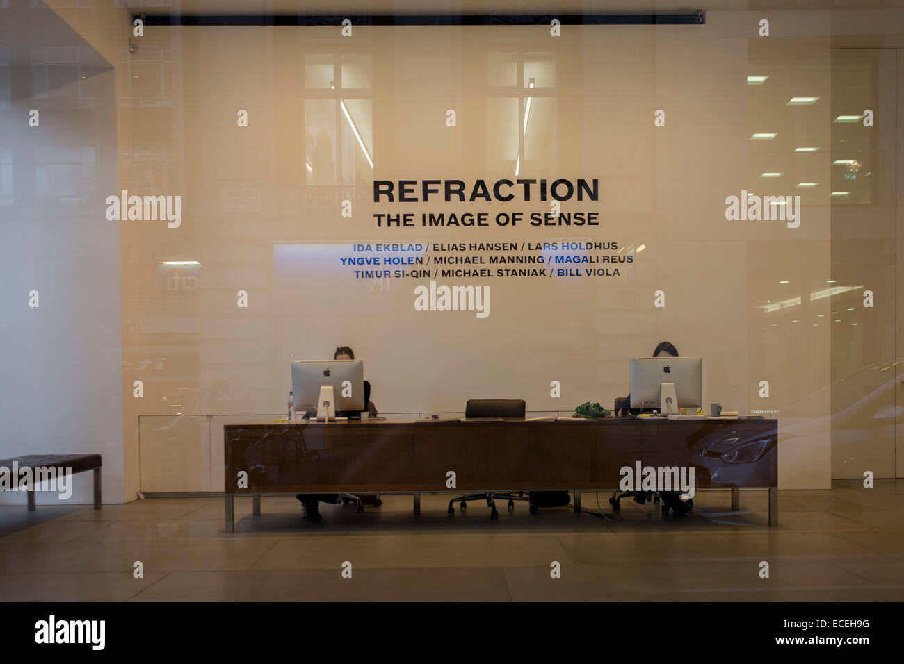 Receptionists work behind computer screen in a central Lndon art gallery. - Stock Image