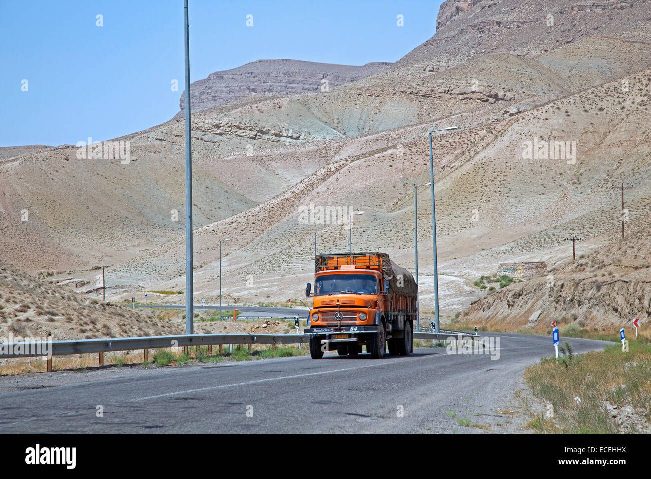 Truck on motorway from Mashhad to Turkmenistan through the Karakum Desert in Iran - Stock Image