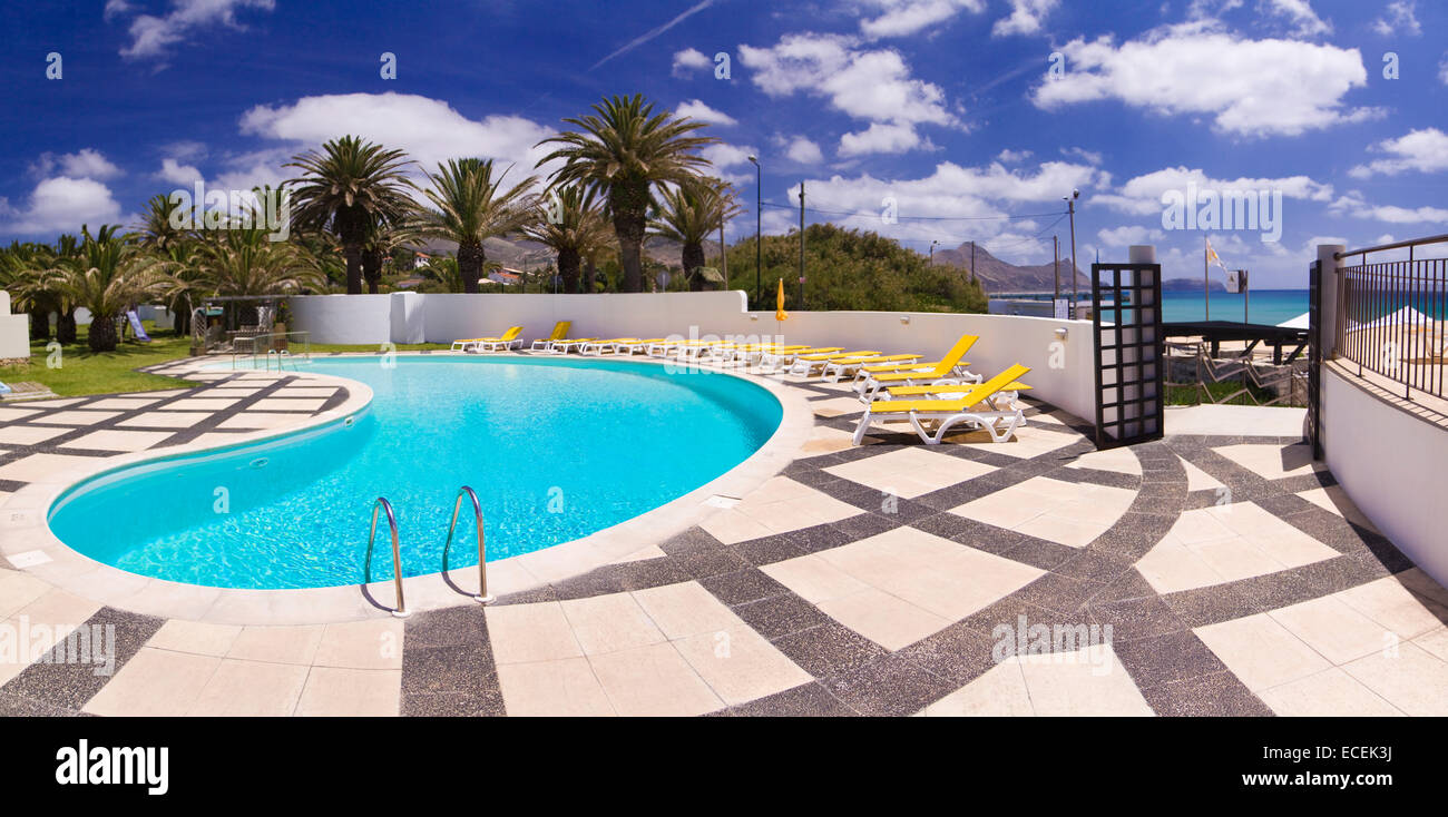 Hotel swimming pool surrounded by deck chairs on the island of Porto Santo, Portugal, panorama - Stock Image