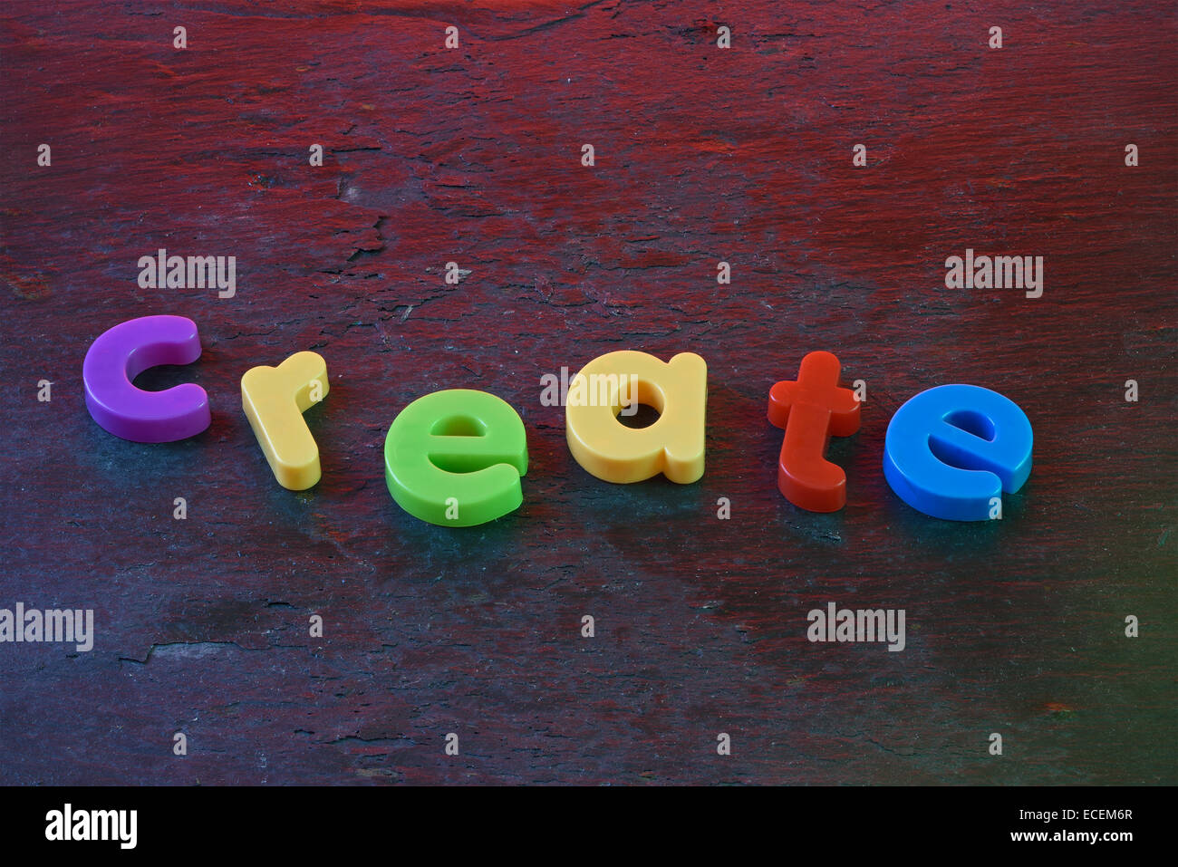 The word 'create,spelled out in colorful fridge magnets on a slate background - Stock Image