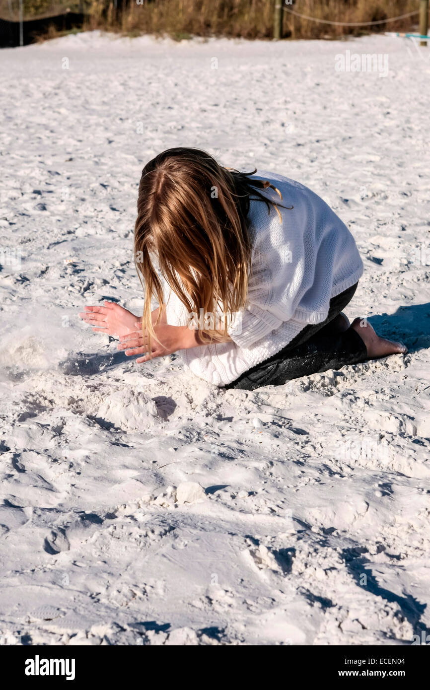 A young pre-teen girl playing in the sanss of Siesta Key beach FL on a cold November day Stock Photo