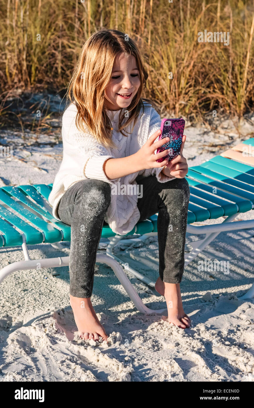 A young Pre-teen girl sits on a beach chair texting and using her iPhone to keep in touch with her friends - Stock Image