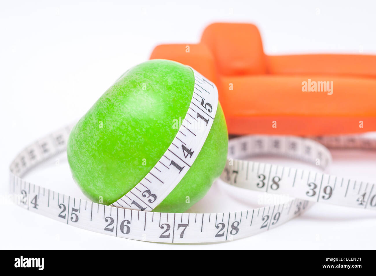 Diet diabetes weight loss concept with tape measure organic green apple and yellow dumbbells on a white background - Stock Image