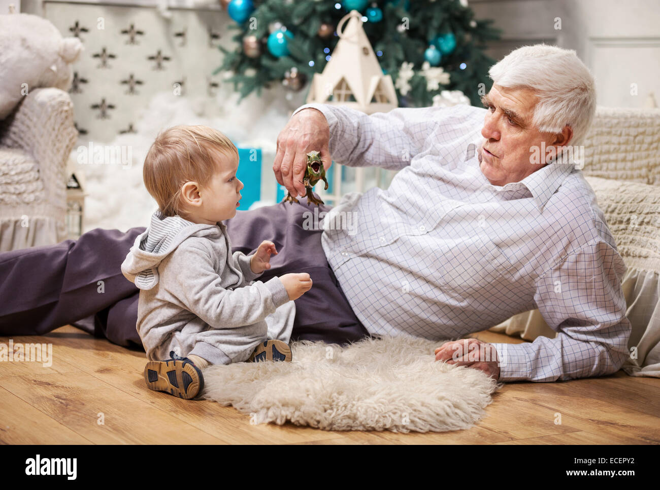 Toddler boy and his grandpa playing with toy dinosaur at Christmas tree - Stock Image
