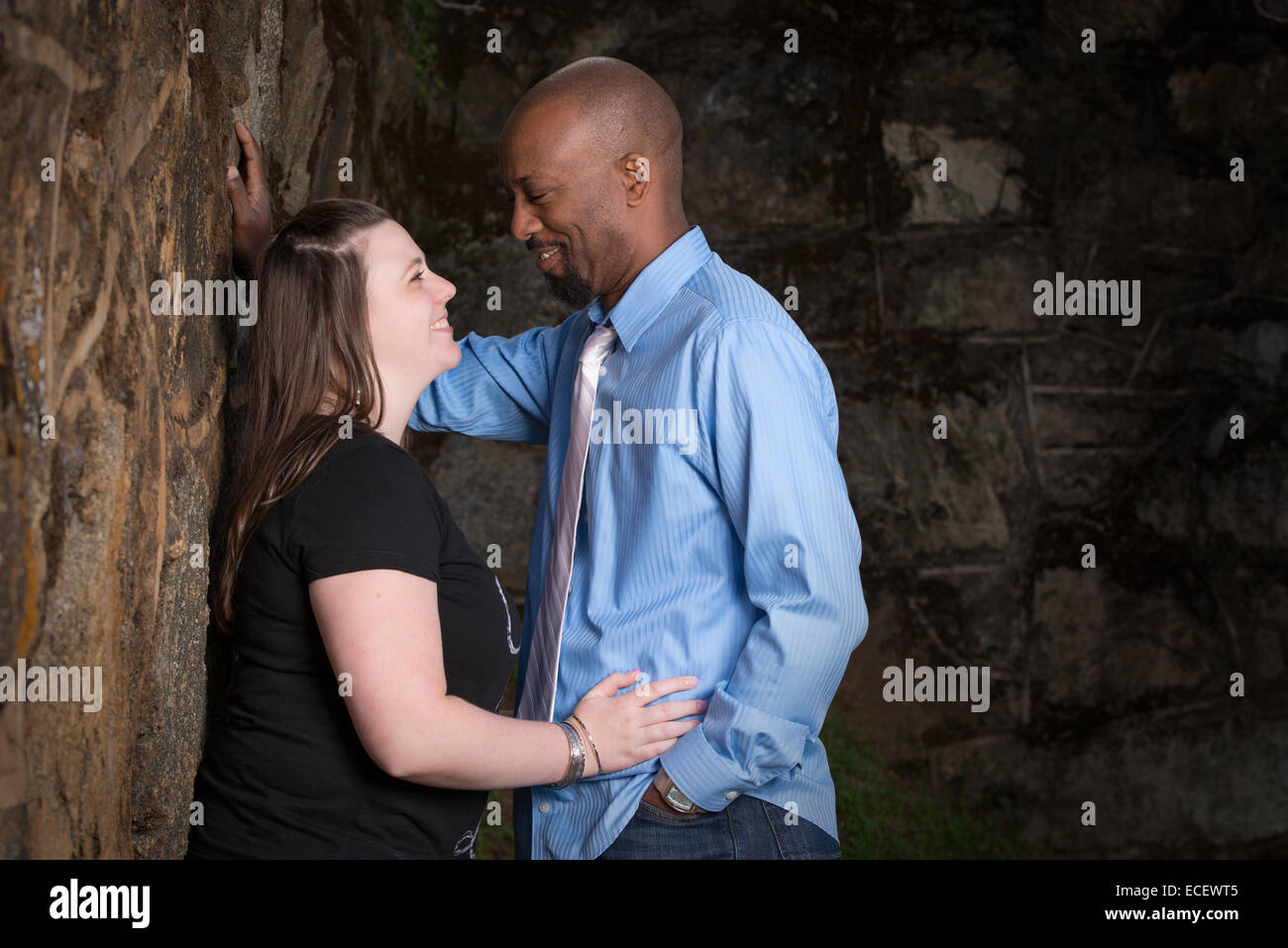 A portrait of an interracial couple looking in each others eyes while smiling. - Stock Image