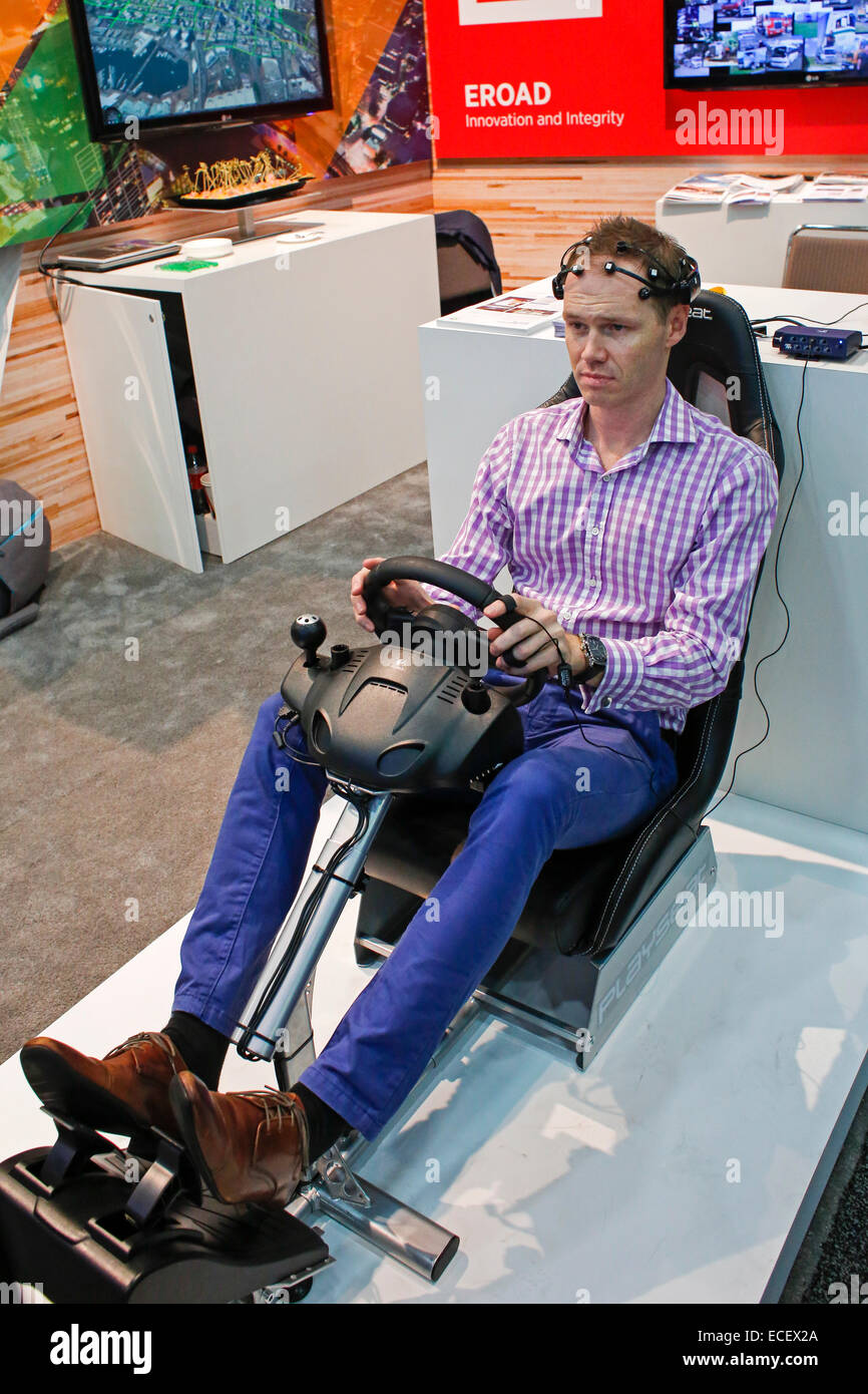 A subject wears sensors to monitor his mental state when presented with distractions while operating a driving simulator. - Stock Image