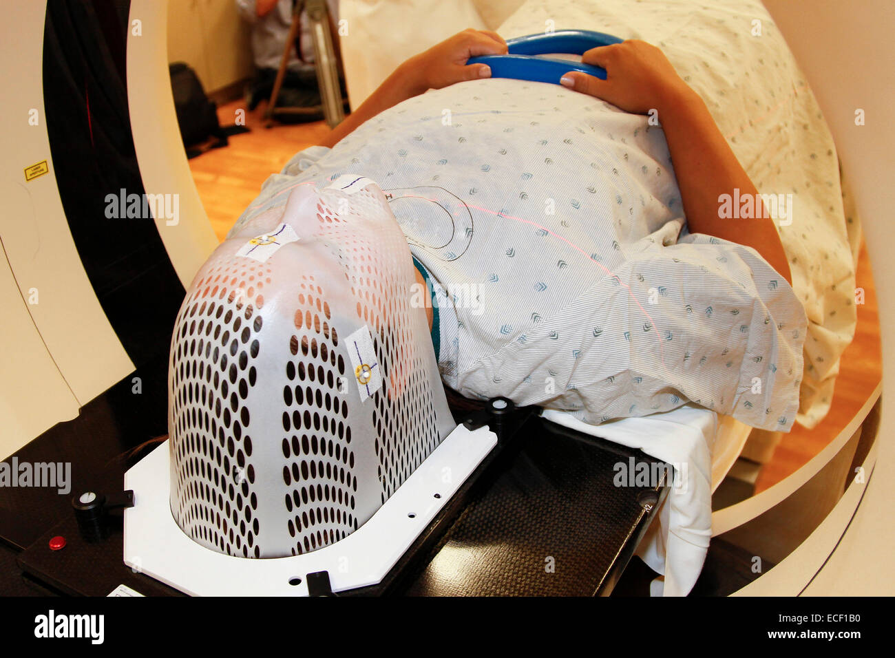 A patient model wearing a short face mask is positioned in a computed tomography (CT) scanner to obtain images of Stock Photo