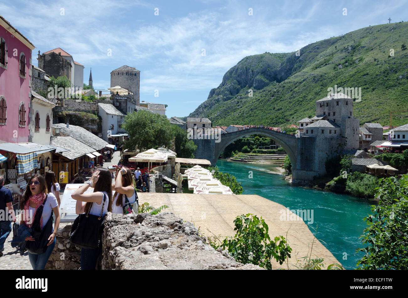 MOSTAR, BOSNIA AND HERZEGOVINA - MAY 18, 2013: Three young woman tourists in Mostar. In the background is the bridge - Stock Image