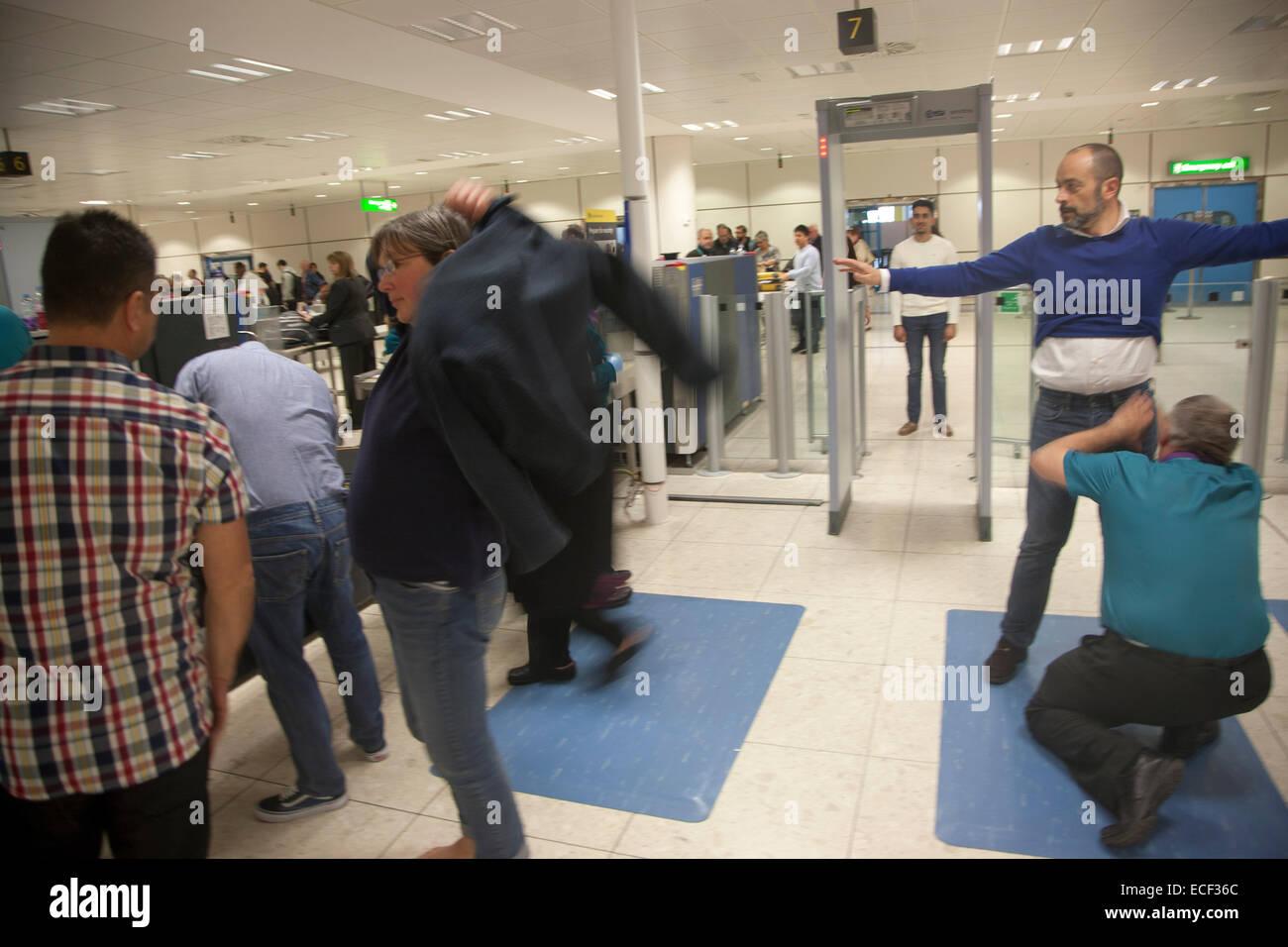 People passing through security screening at Gatwick airport, England, UK - Stock Image