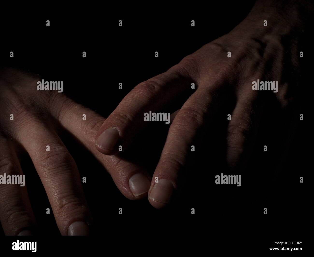 Man's hands on black background - Stock Image