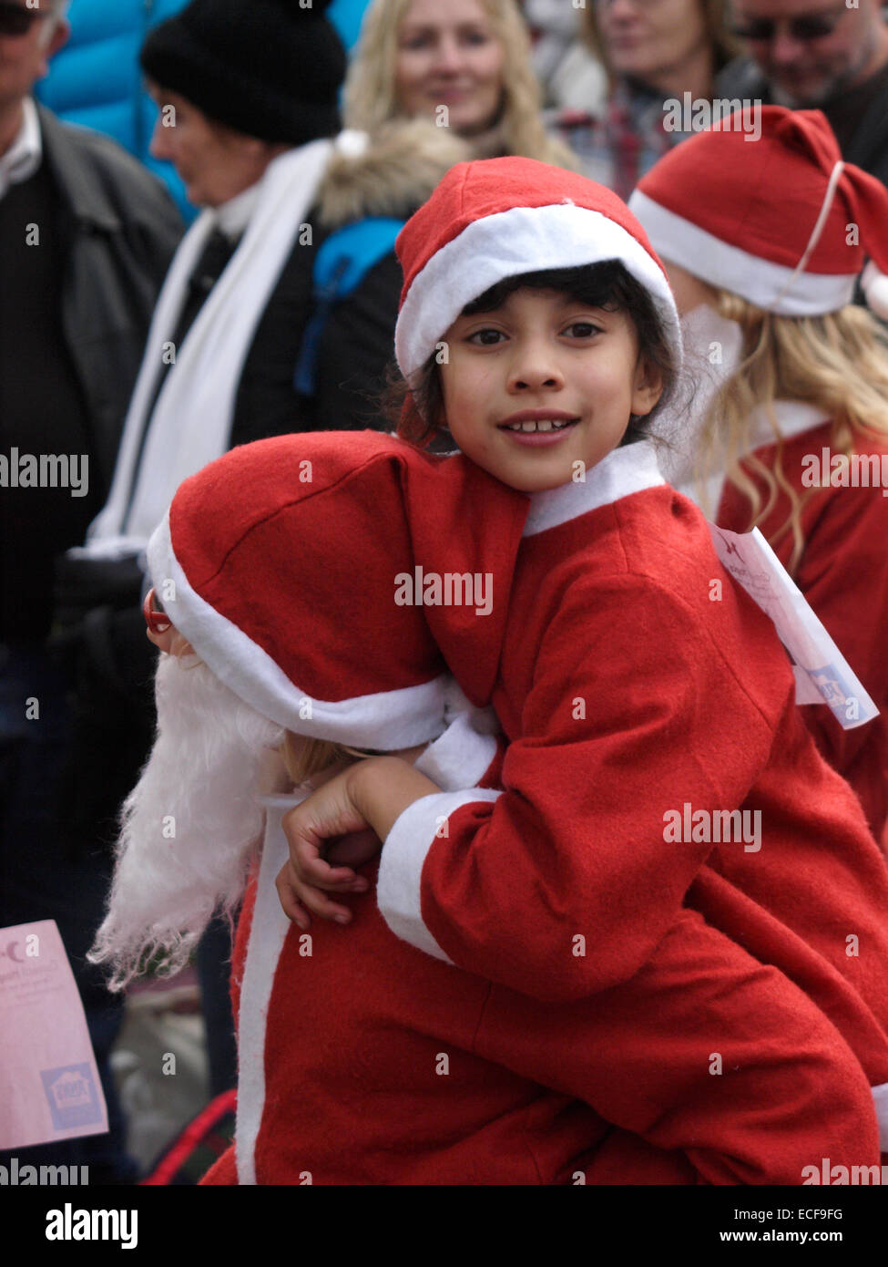 Child give a piggy back to another child, dressed in Santa suits for the Charity Santa run at the Padstow Christmas - Stock Image