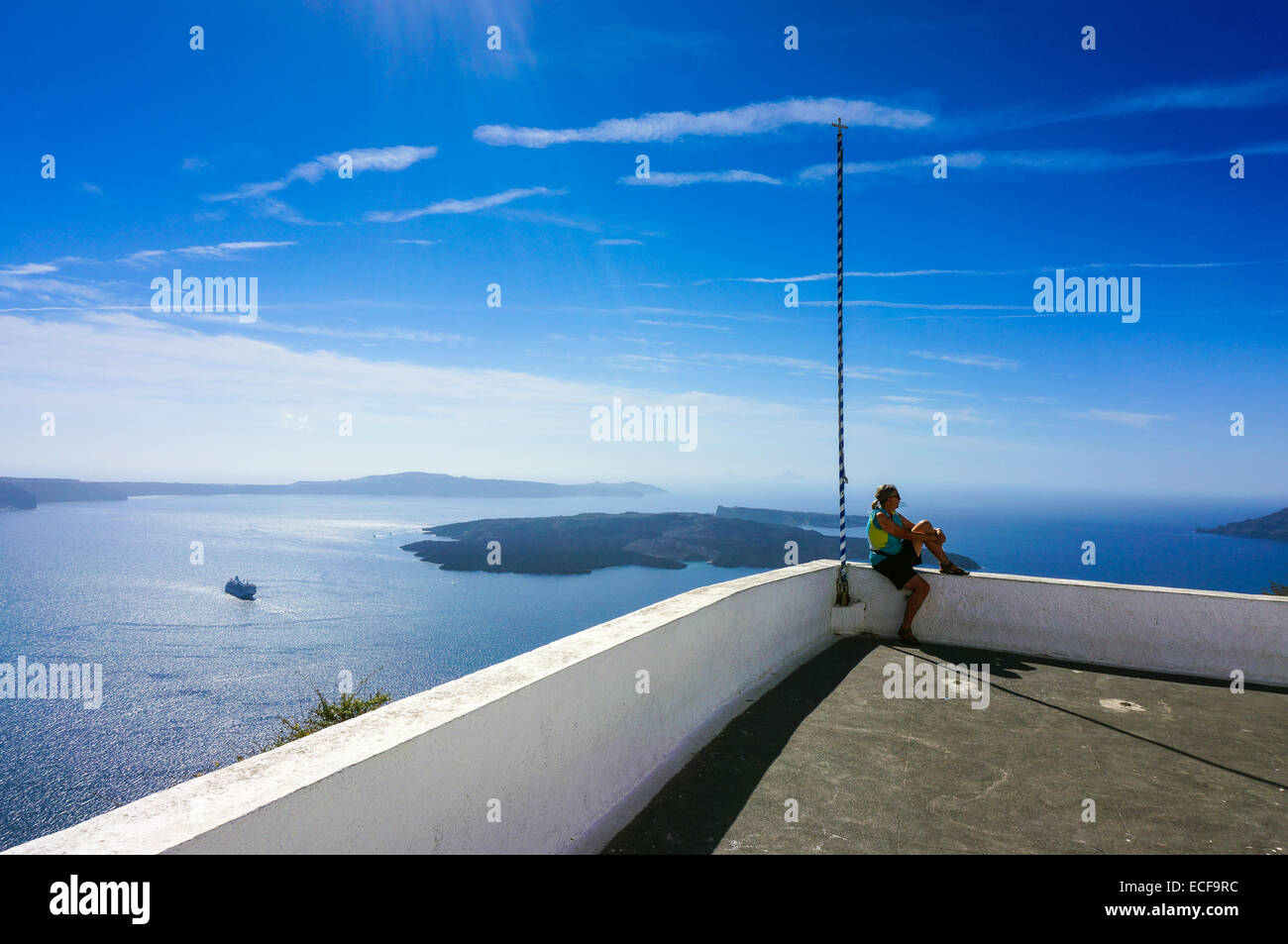 Solitary female figure sat on white wall above caldera - Stock Image