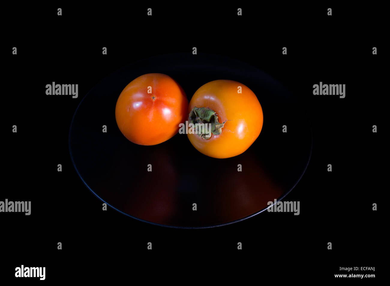 Ripe Golden two persimmons on plate - Stock Image