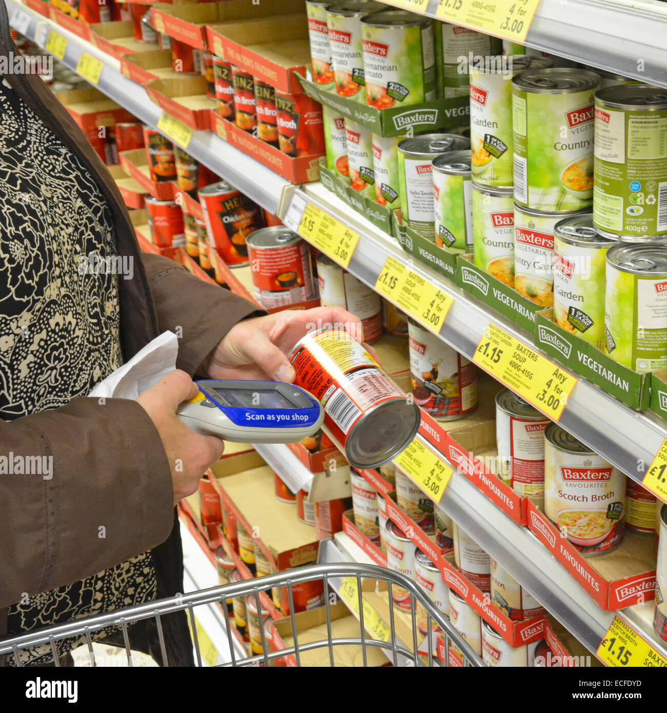 Tesco supermarket shopper using handheld scan as you shop device to record purchases on digital display for downloading - Stock Image