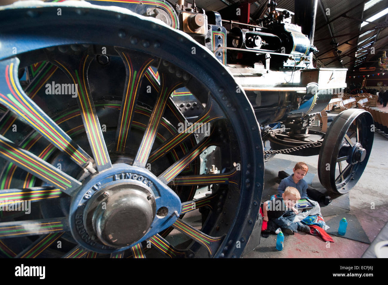Two young brothers sit under the giant decorative wheels of Traction Engine 'The Champion' built by Ruston - Stock Image
