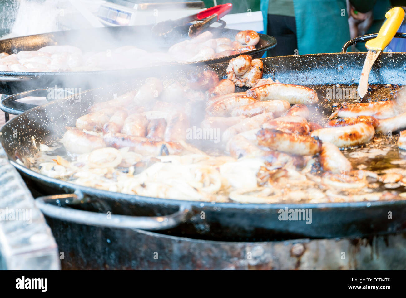 Sausages & onions cooking in a giant frying pan, outside catering, UK. - Stock Image