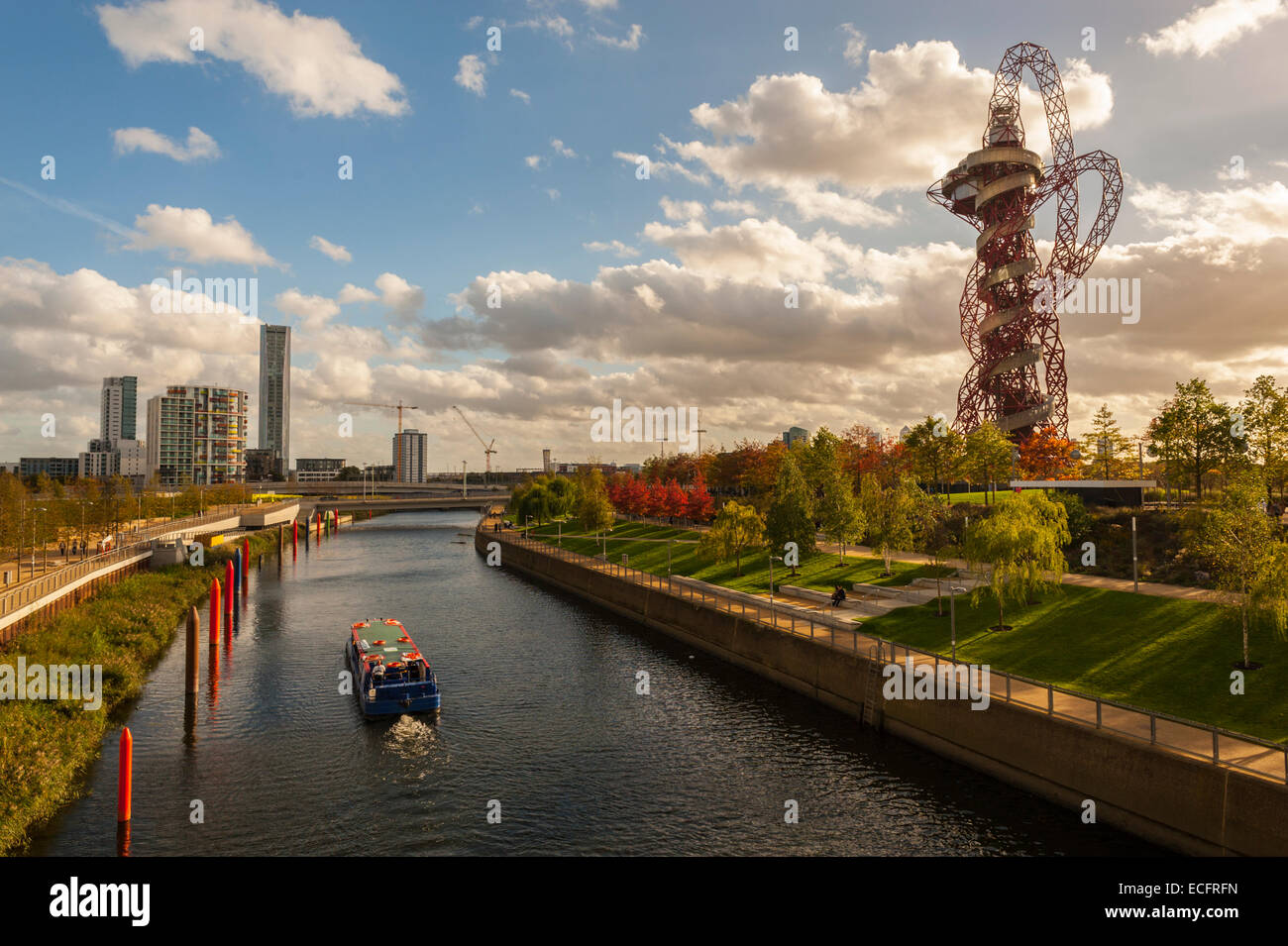 Boat on the river Lea with Stratford City and the orbital tower in the background. - Stock Image
