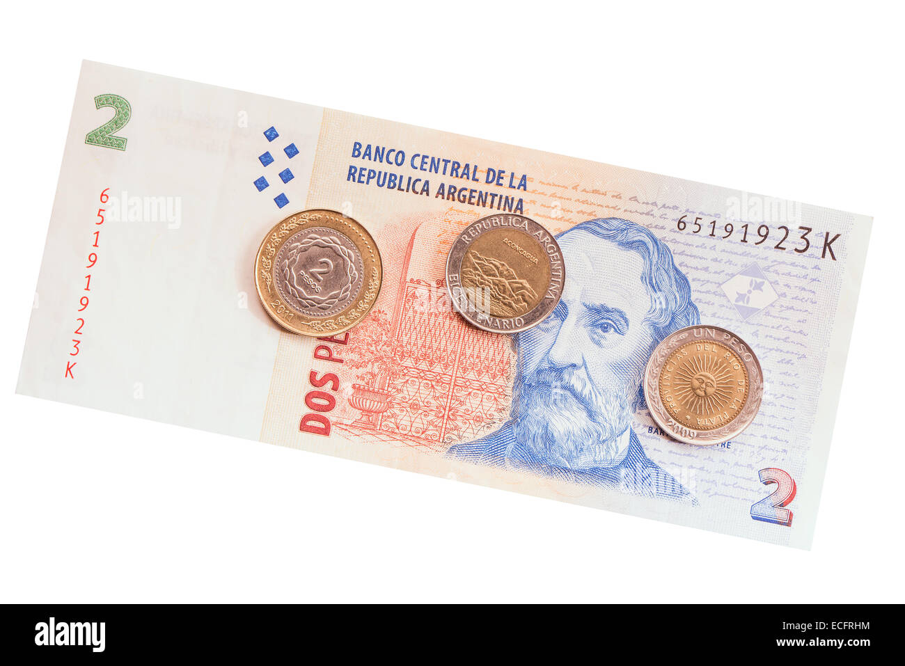Argentinean coins on two pesos banknote background. - Stock Image