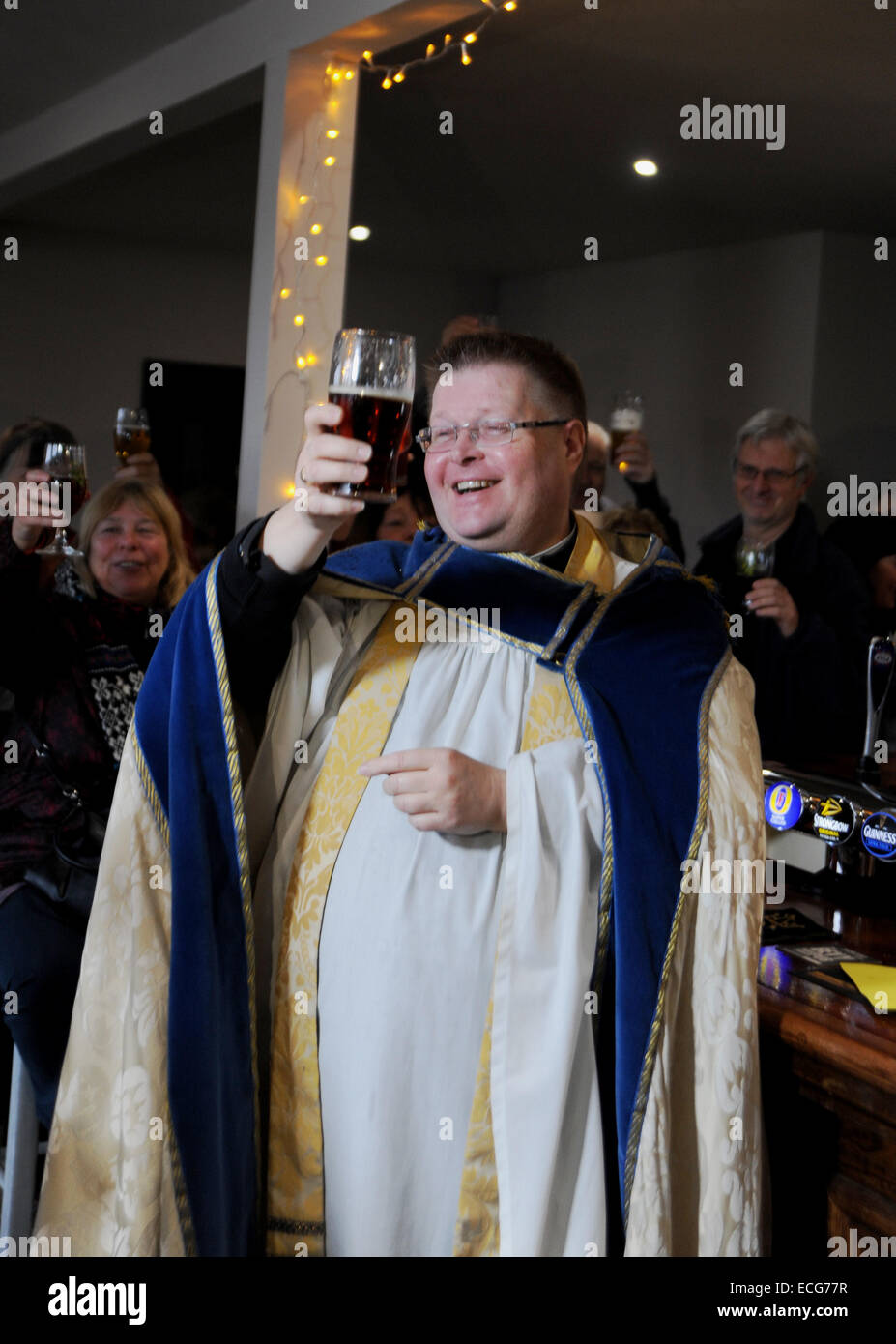 Brighton UK 12th December 2014 - Local Moulsecoomb vicar Father John Hall blesses the newly refurbished Bevy pub - Stock Image